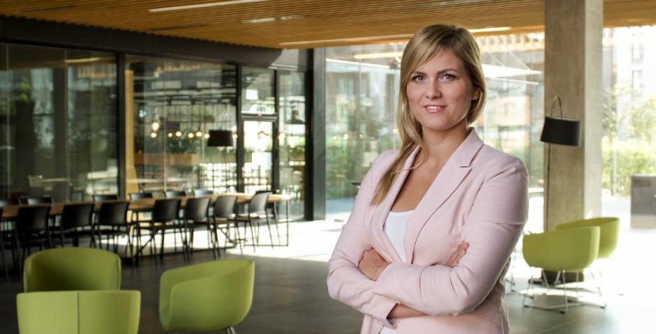 Marta Rajnholc-Kondej - pracowniczka księgowości stojąca w przestrzeni biurowca